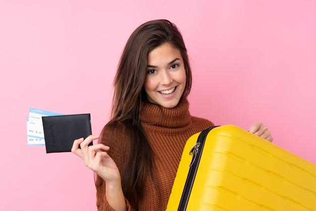 Menina adolescente sobre parede rosa isolada em férias com mala e passaporte Foto Premium