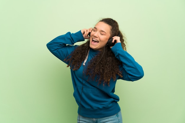 Menina adolescente sobre parede verde, ouvindo música com fones de ouvido Foto Premium