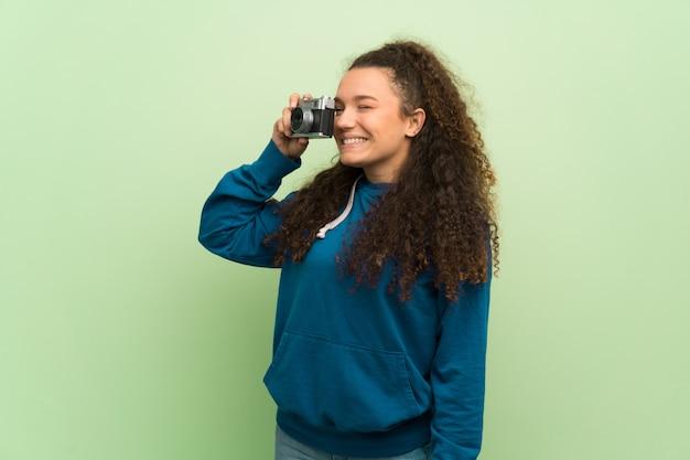 Menina adolescente sobre parede verde segurando uma câmera Foto Premium