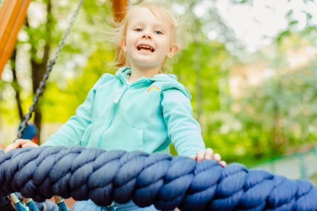 Menina adorável 4 anos velha que tem o divertimento em um balanço da corda redonda em um campo de jogos no dia de verão. Foto Premium