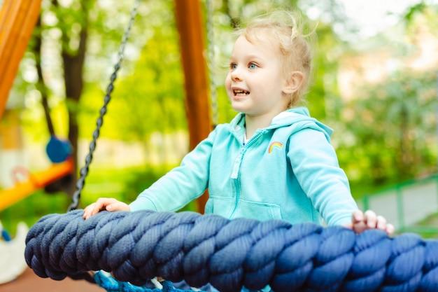 Menina adorável 4 anos velha que tem o divertimento em um balanço da corda redonda em um campo de jogos. Foto Premium
