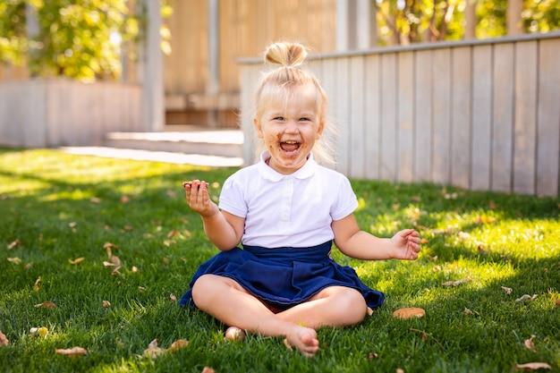 Menina adorável bebê caucasiano adorável criança sentado e comendo Foto Premium
