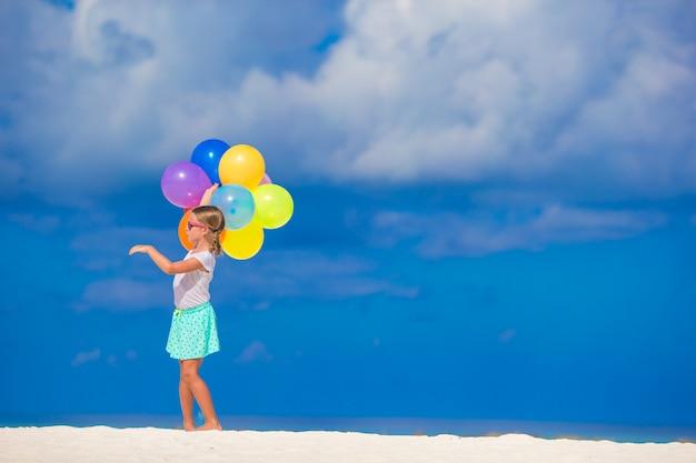 Menina adorável brincando com balões na praia Foto Premium