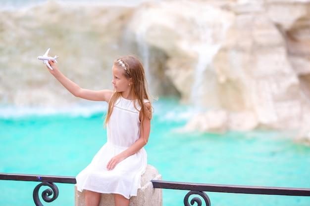 Menina adorável com a fonte do trevi do fundo do avião do brinquedo, roma, itália. Foto Premium