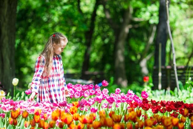 Menina adorável com flores no jardim de tulipas Foto Premium