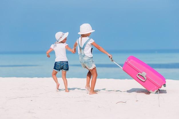 Menina adorável com grande bagagem durante as férias de verão Foto Premium