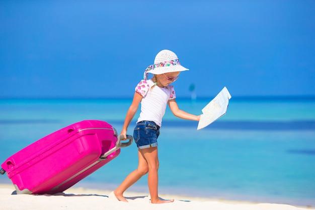 Menina adorável com mala grande na praia tropical branca Foto Premium