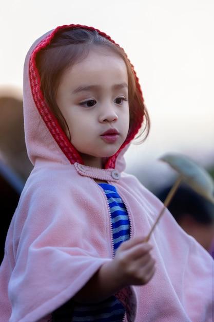 Menina adorável da criança que tem o divertimento no dia de inverno. as crianças brincam ao ar livre. moda de inverno para crianças. Foto Premium