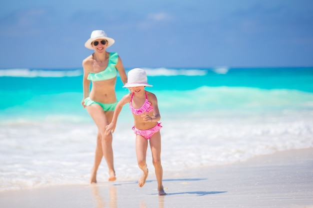 Menina adorável e jovem mãe na praia tropical Foto Premium