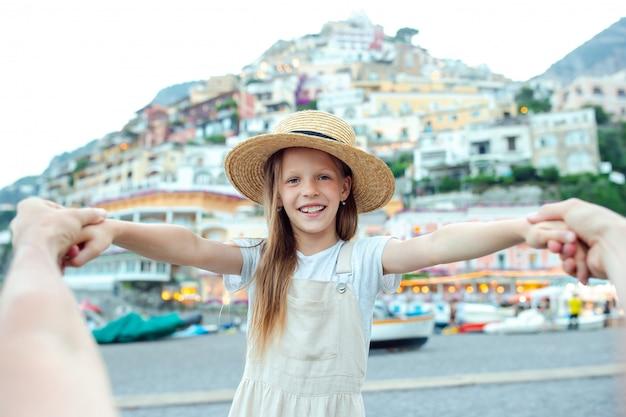 Menina adorável em dia de verão quente e ensolarado na cidade de positano, na itália Foto Premium