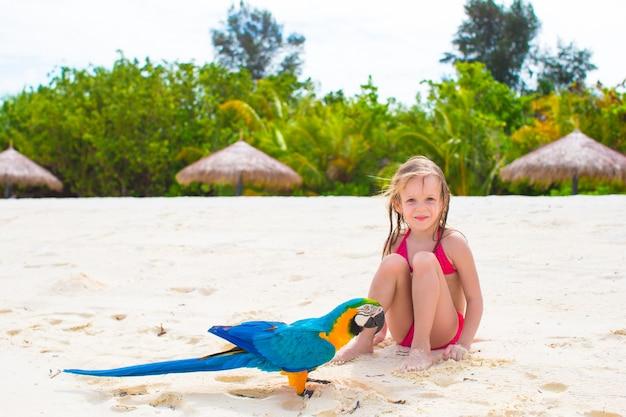 Menina adorável na praia com papagaio colorido Foto Premium