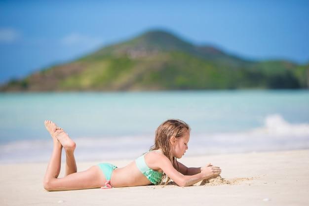 Menina adorável na praia se divertindo muito em águas rasas Foto Premium
