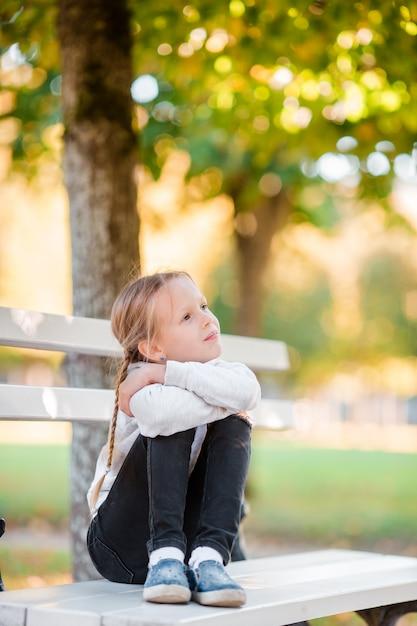 Menina adorável no dia bonito do outono ao ar livre. menina no banco em queda Foto Premium
