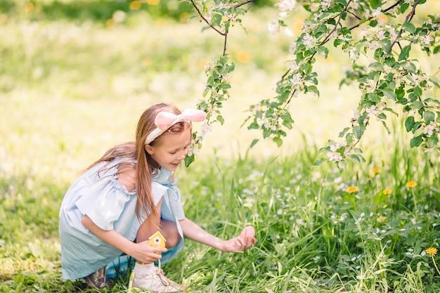 Menina adorável no jardim de maçã florescendo no lindo dia de primavera Foto Premium