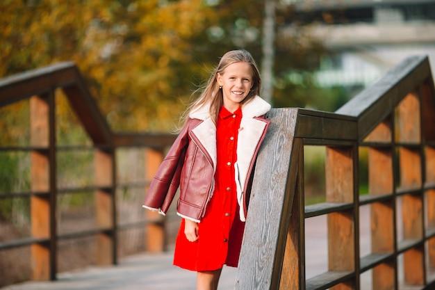 Menina adorável no lindo dia de outono ao ar livre Foto Premium