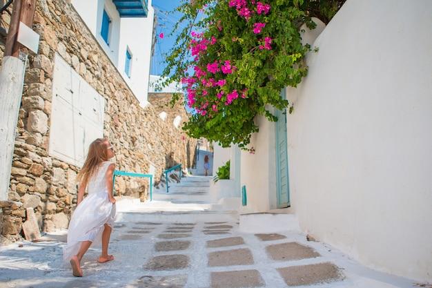 Menina adorável no vestido branco que tem o divertimento ao ar livre. garoto na rua da típica aldeia tradicional grega com paredes brancas e portas coloridas na ilha de mykonos, na grécia Foto Premium