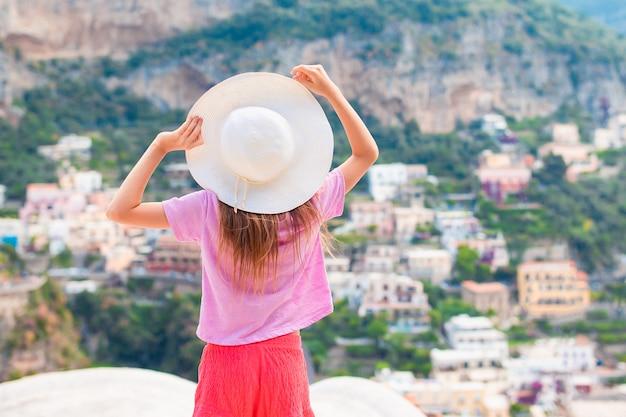 Menina adorável num dia quente e ensolarado de verão na cidade de positano na itália Foto Premium