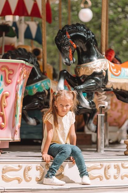 Menina adorável perto do carrossel ao ar livre Foto Premium