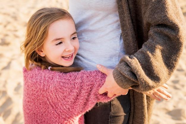 Menina adorável que abraça a mãe tiro médio Foto gratuita