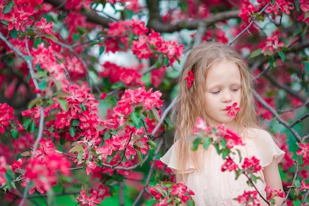 Menina adorável que aprecia o dia de mola no jardim de florescência da maçã Foto Premium