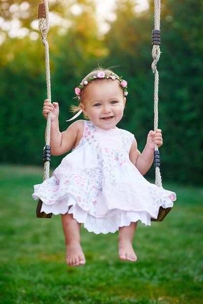 Menina adorável que aprecia um passeio do balanço em um campo de jogos em um parque Foto Premium