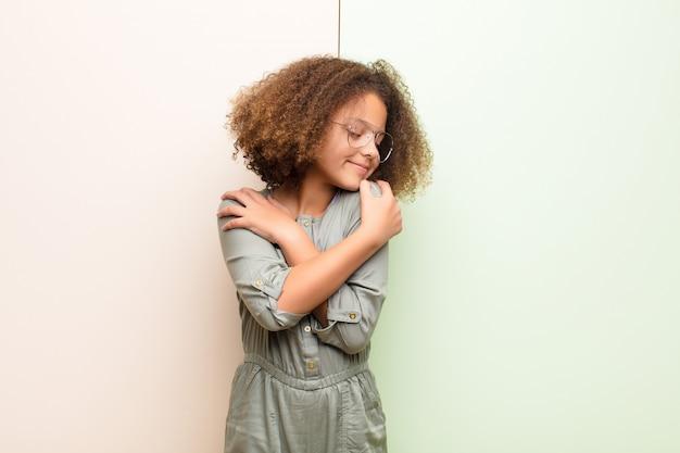 Menina afro-americana se sentindo apaixonado, sorrindo, abraçando e abraçando a si mesma, ficando solteira, sendo egoísta e egocêntrica contra a parede plana Foto Premium
