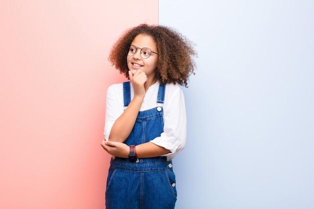 Menina afro-americana sorrindo com uma expressão feliz e confiante com a mão no queixo, pensando e olhando para o lado por cima do muro Foto Premium