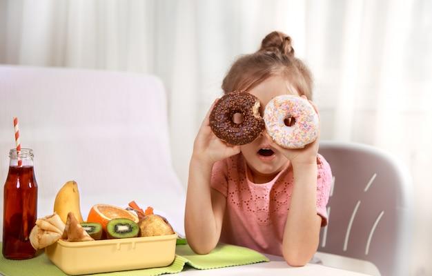 Menina alegre bonita comendo um donut Foto gratuita