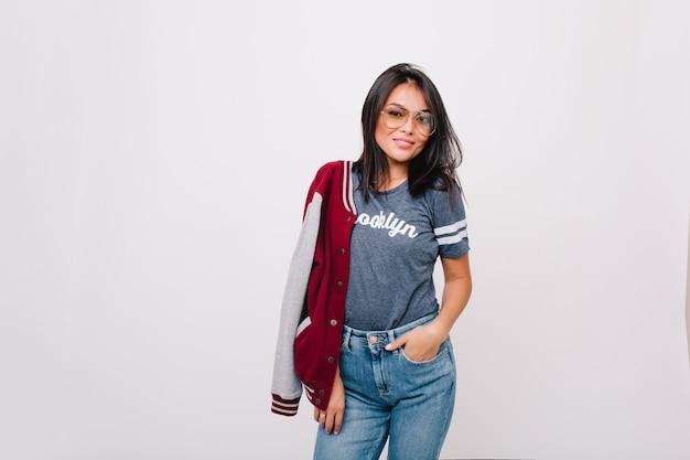 Menina alegre e magro em camiseta cinza e calça jeans posando com a mão no bolso e sorrindo. modelo feminino de cabelos negros em jeans e homem-bomba em pé. Foto gratuita
