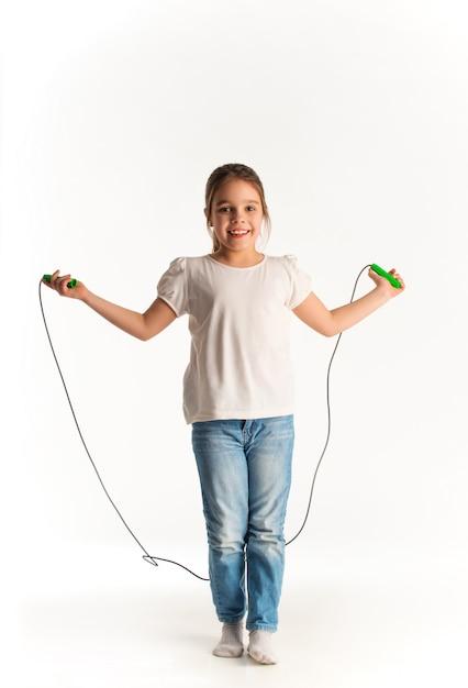 Menina alegre em roupas casuais, pulando na corda Foto Premium