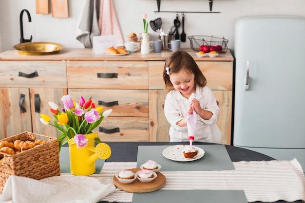 Menina alegre fazendo bolinho Foto gratuita