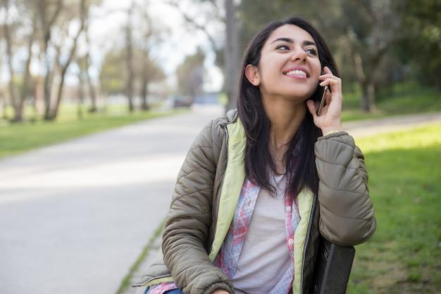 Menina alegre feliz estudante falando no celular no parque Foto gratuita