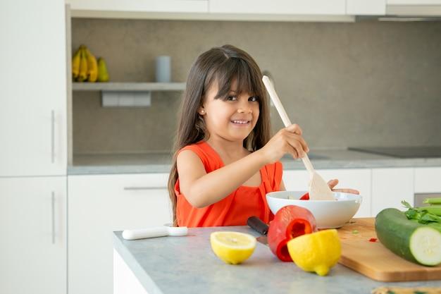 Menina alegre jogando salada na tigela com uma colher de pau grande. linda criança, passar um tempo em casa durante a pandemia, cozinhar vegetais, posando, sorrindo para a câmera. aprendendo a cozinhar conceito Foto gratuita