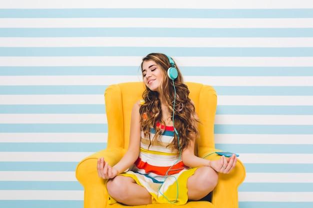 Menina alegre meditando enquanto está sentado em uma pose de lótus na parede listrada azul. bela jovem com vestido colorido, relaxando na poltrona amarela e ouvindo música relaxante. Foto gratuita