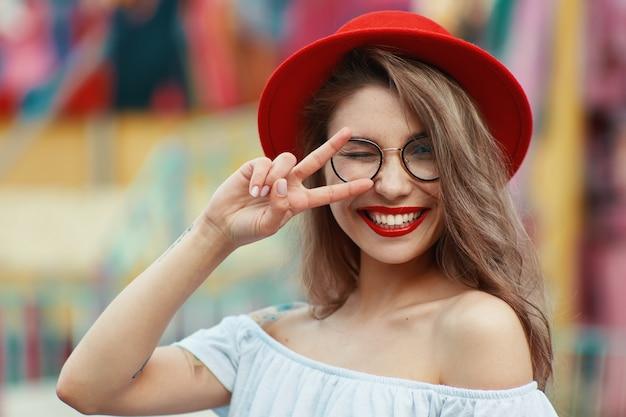 Menina alegre, piscando e sorrindo enquanto mostra o sinal da vitória Foto gratuita