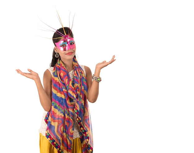 Menina alegre sorridente usando máscara de carnaval e mostrando placa isolada no fundo branco Foto Premium