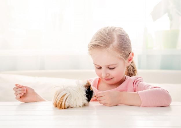 Menina alimentando seu porquinho da índia Foto Premium