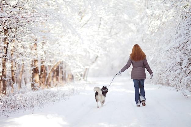Menina anda com um cachorro no parque no inverno Foto Premium