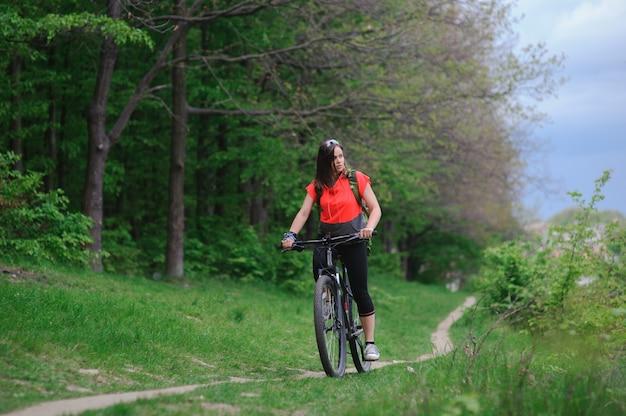 Menina andando de bicicleta na floresta Foto Premium