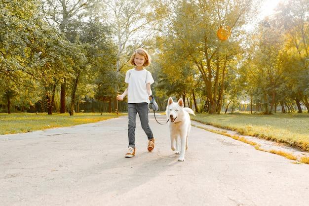 Menina andando na estrada no parque com um cão husky branco Foto Premium