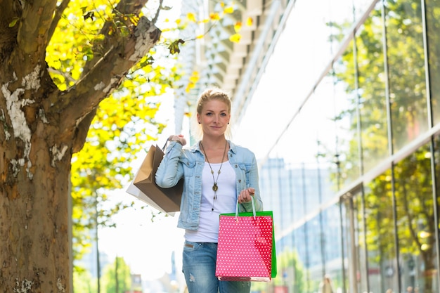 Menina andando na rua com sacolas de compras Foto Premium