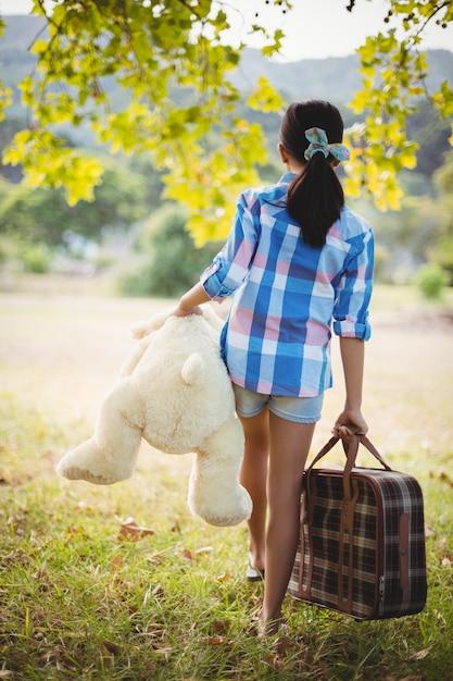 Menina andando no parque com uma mala e ursinho de pelúcia Foto Premium