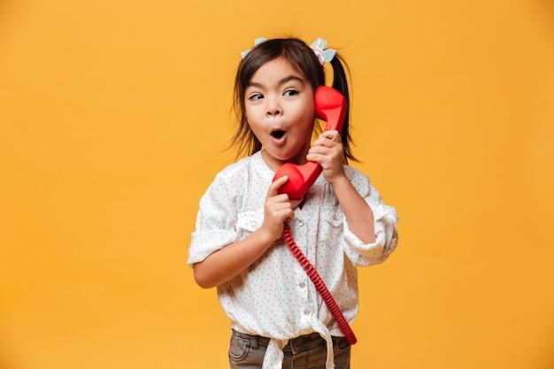Menina animada chocada falando pelo telefone retrô vermelho. Foto gratuita