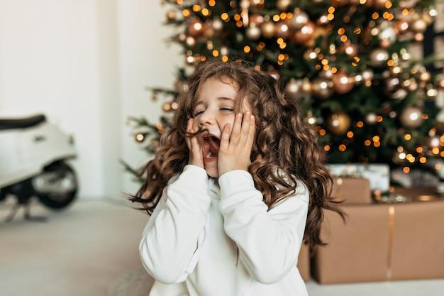 Menina animada com emoções de surpresa cobrindo o rosto com as mãos, sentada em frente à árvore de natal e esperando os presentes de natal Foto gratuita