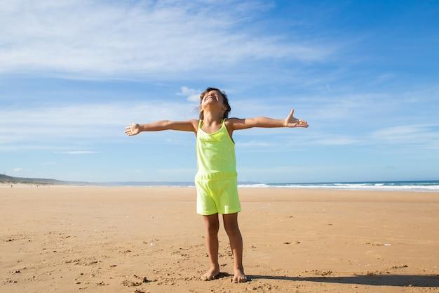 Menina animada com roupas de verão, em pé com as mãos voadoras na praia e virando o rosto para cima Foto gratuita