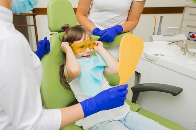 Menina animada no dentista olhando no espelho Foto gratuita