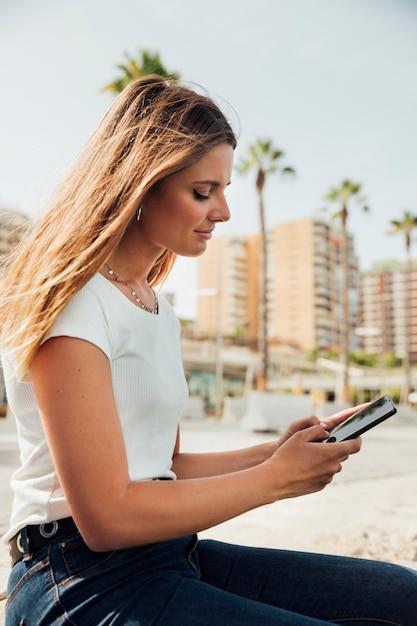 Menina ao ar livre close-up, segurando o telefone Foto gratuita