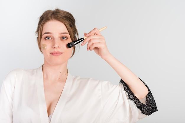 Menina, aplicando, mesma, cosmético, produto Foto gratuita