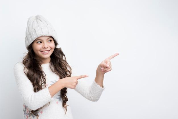 Menina apontando com os dedos para a esquerda Foto gratuita