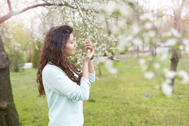 Menina, apreciando o cheiro em um jardim florido Foto Premium